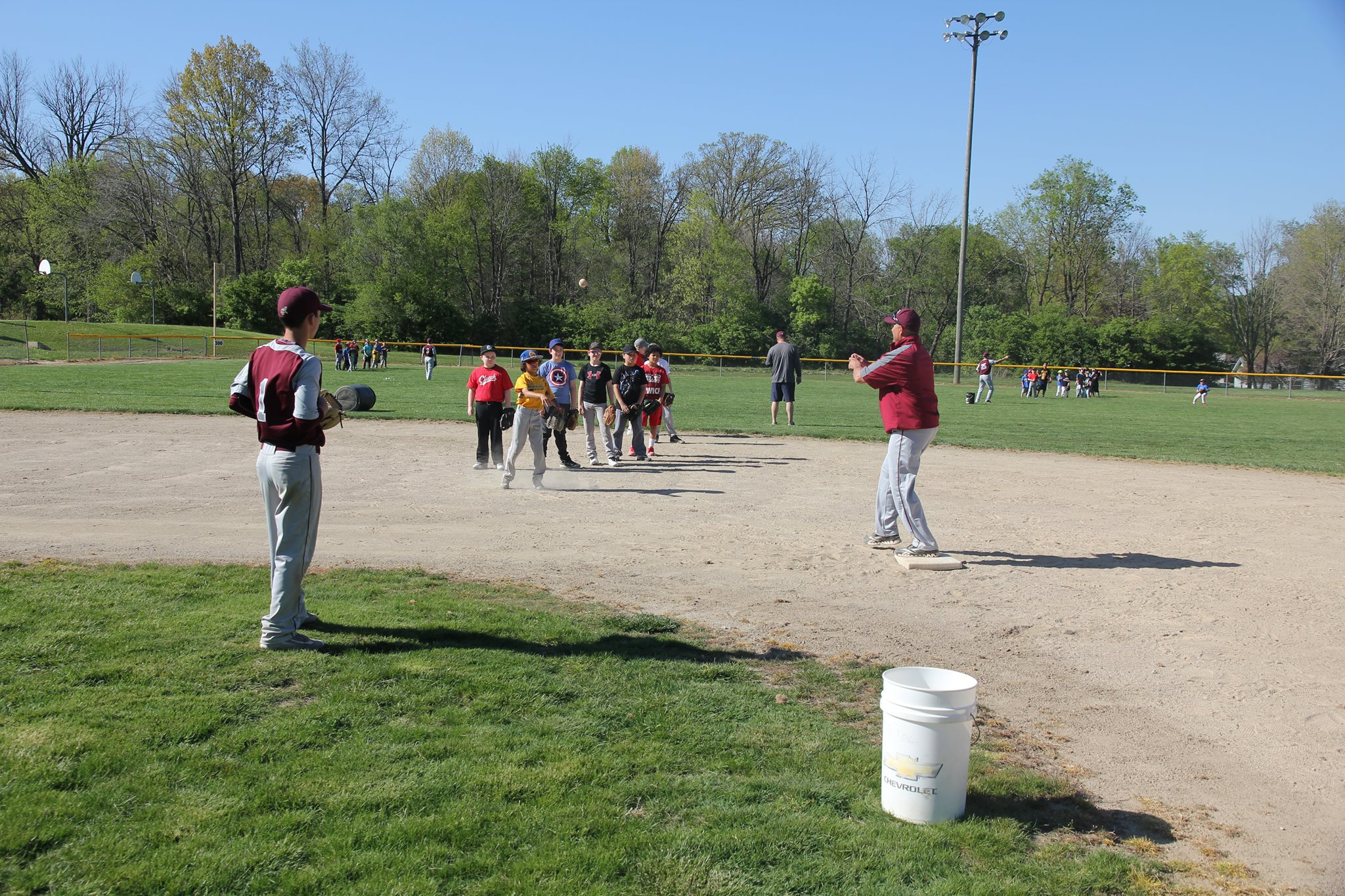 Danville High School JV Head Coach Mike Dokey working with players on fielding ground balls and throwing to a base for a force out.